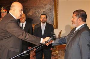 Mahmoud Mekki (left) shaking the hand of President Morsi (right)